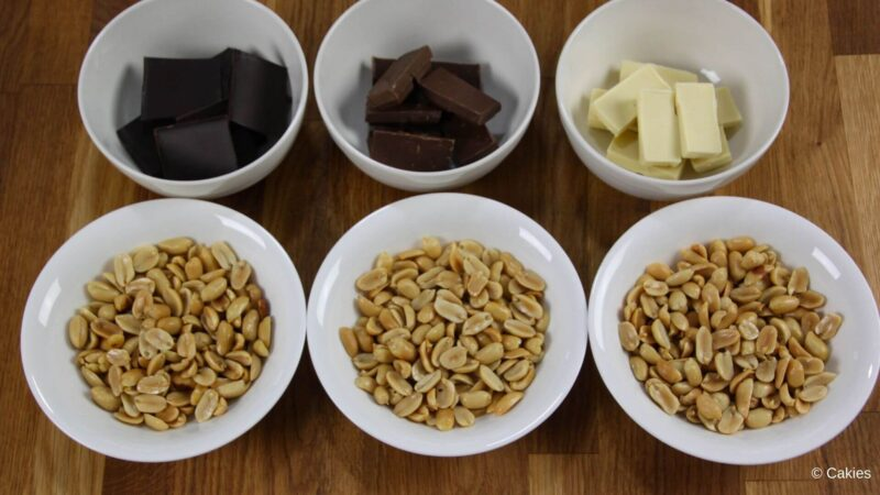 6 bowls on a wooden surface. 3 bowls with peanuts, 1 bowl with dark chocolate chunks, 1 bowl with white chocolate chunks, 1 bowl with milk chocolate chunks
