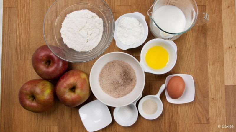 Ingredients for Dutch apple fritters on a wooden surface.