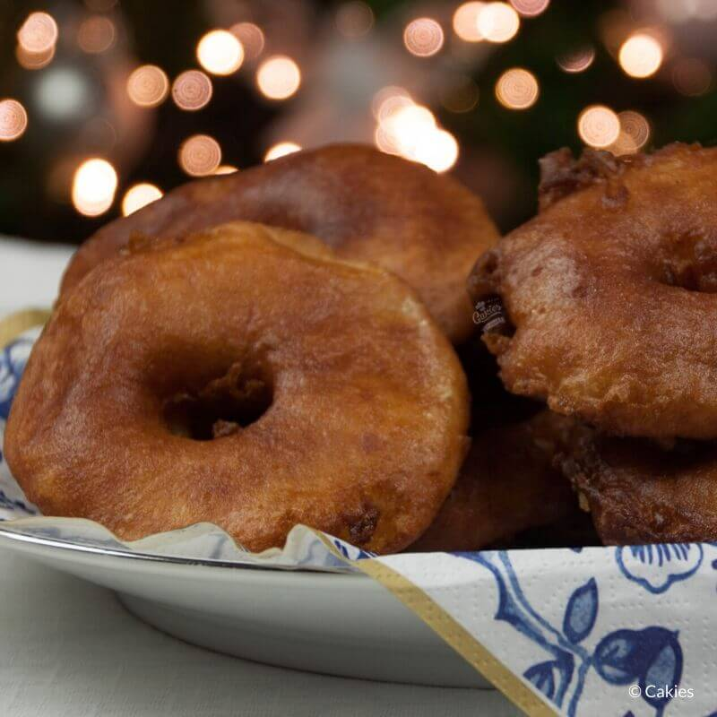 Dutch Apple Fritters on a plate with lights in the background