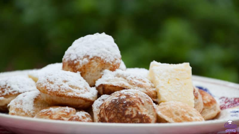 Poffertjes displayed on a plate, sprinkled with confectioners' sugar and a knob of butter on the side
