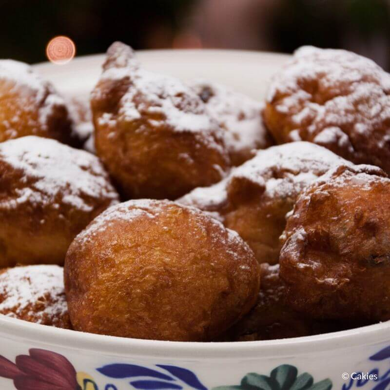 oliebollen in a bowl dusted with confectioners' sugar