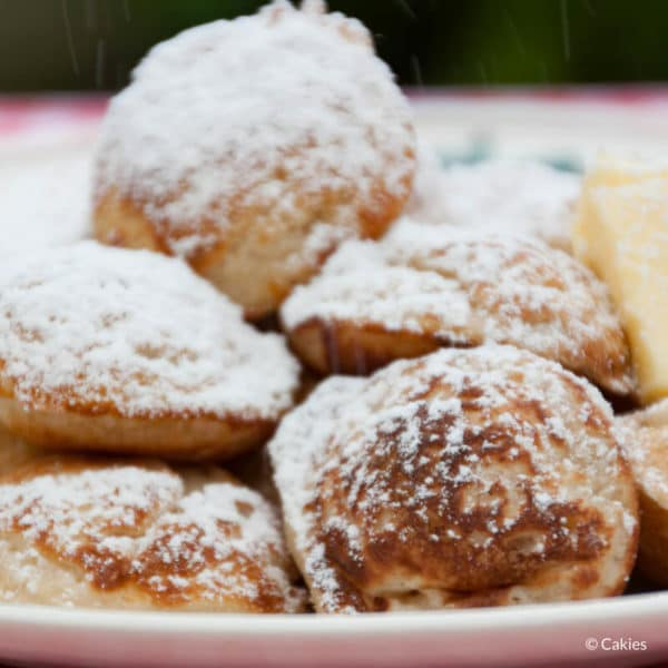 Poffertjes are a traditional Dutch treat. Mini, fluffy pancakes made with yeast and buckwheat flour. Typically eaten sprinkled with confectioner's sugar. #poffertjes #dutchrecipe #dutchrecipes #minipancakes
